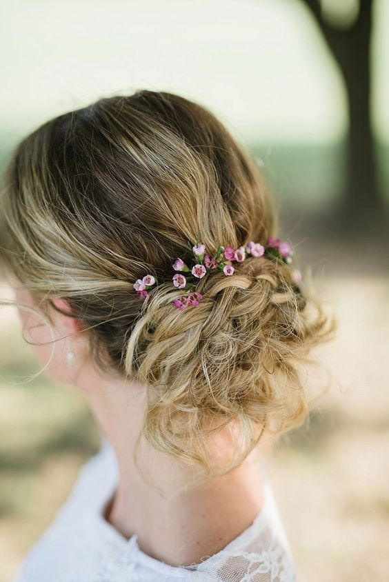 a textural messy updo with braids, a bump and little flowers to add a touch of color