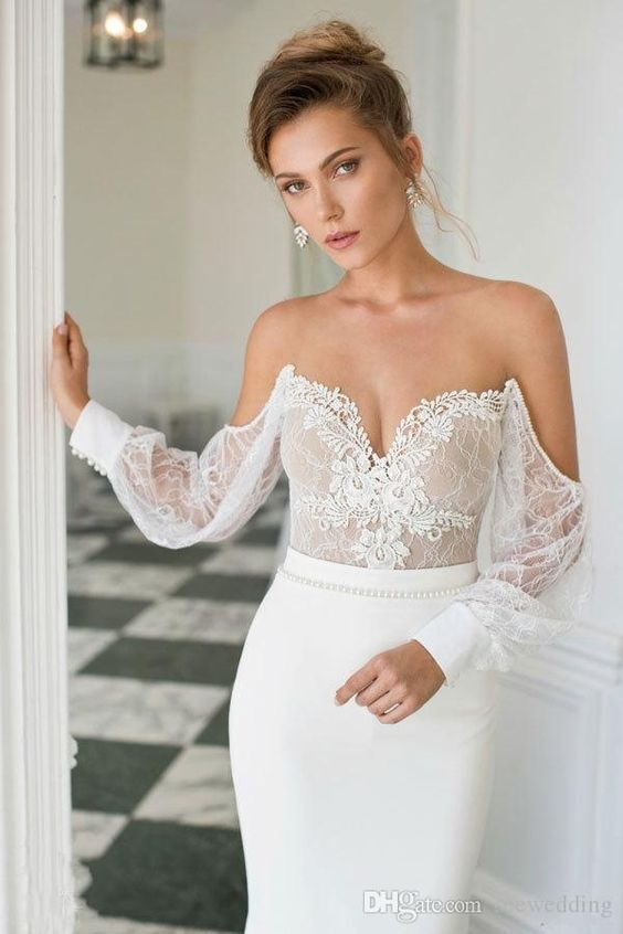 a wow off the shoulder wedding gown with a lace bodice and long sleeves and a plain sheath skirt
