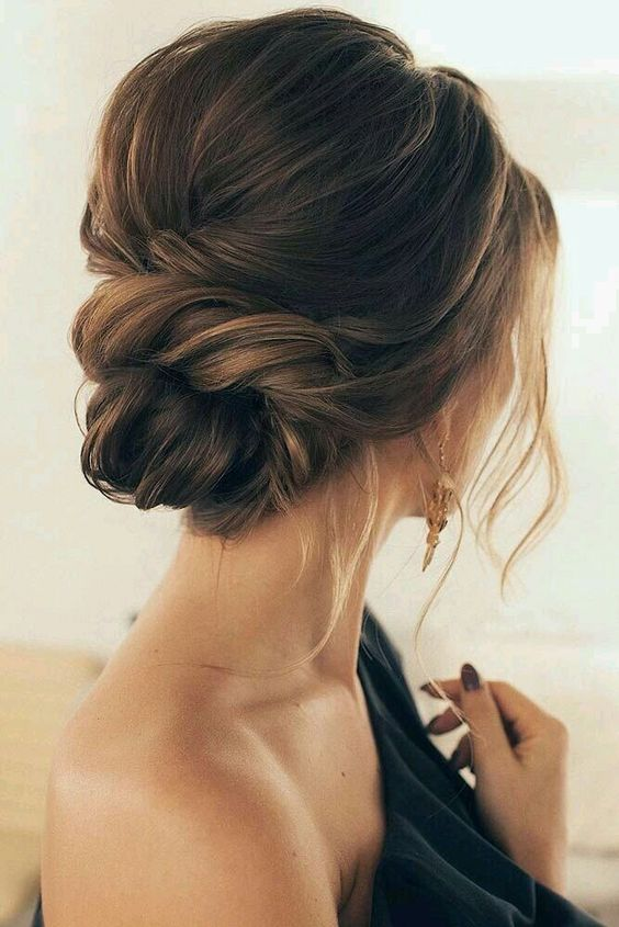 an elegant and effortless twisted low bun with a bump and some locks plus messy details