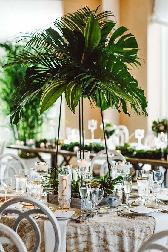 a lush tropical wedding centerpiece of tropical leaves on a tall black metal stand and a matching decoration on the table