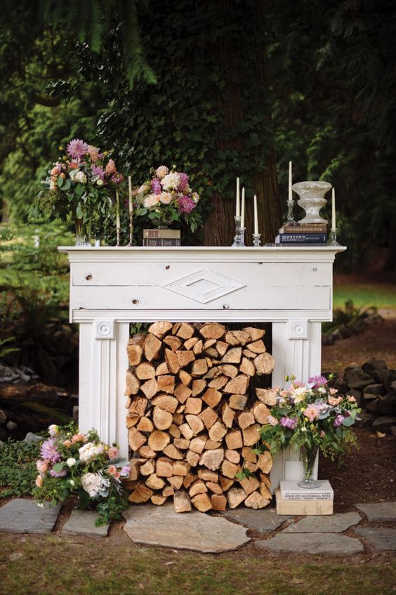a vintage white mantel with candles, bloom decor and firewood stacked inside the mantel