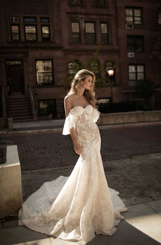 an off the shoulder sheer lace embellished fit and flare wedding dress with a train