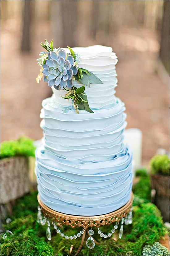 an ombre blue ruffle wedding cake decorated with greenery and a pale succulent