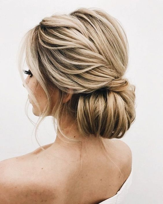 an oversized low bun with a twisted braid on the side and some waves down for a refined feel