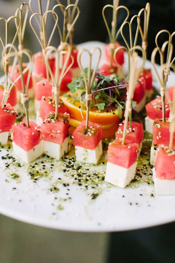 mozzarella and watermelon bites sprinkled with sesame seeds and with sauce
