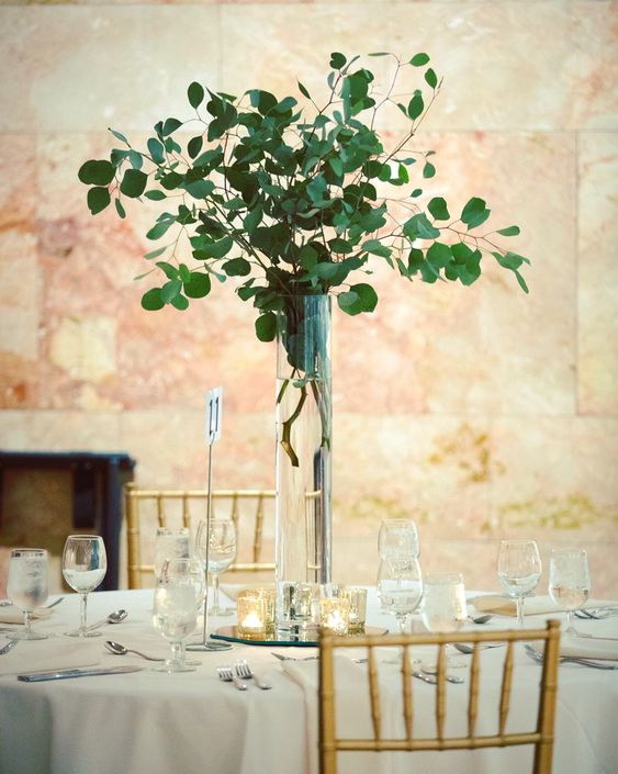 a tall silver eucalyptus centerpiece in a clear vase is an ultra-modern idea of wedding decor