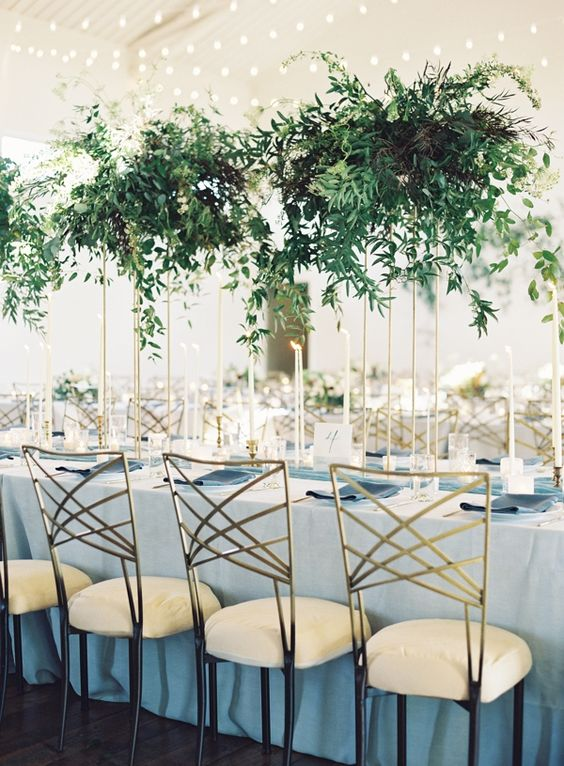 stylish modern wedding centerpiece of lush cascading greneery on tall gold stands