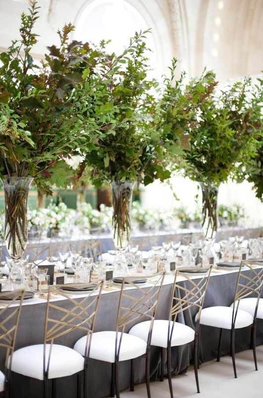 such tall lush textural greenery centerpieces in clear vases create a feeling of outdoors right in your venue