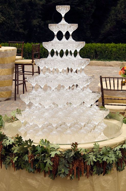 a tower of crystal champagne glasses waits to be filled on a low table decorated with leaves