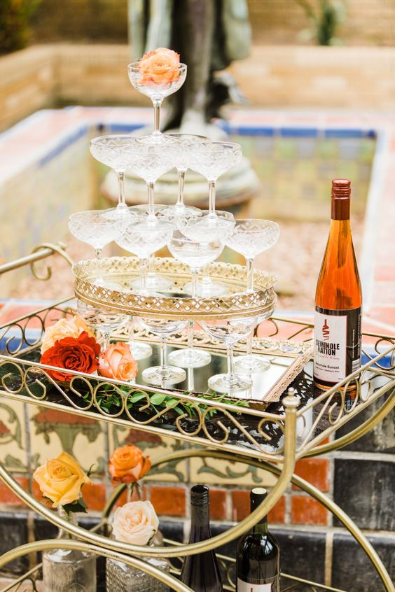 a vintage and refined bar cart with a champagne tower that is accented with a refined metal decoration