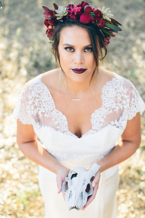 an aubergine lip and a super bright floral crown spruce up the bridal look making it very edgy