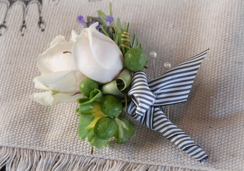 DIY floral boutonniere with berries and ribbon