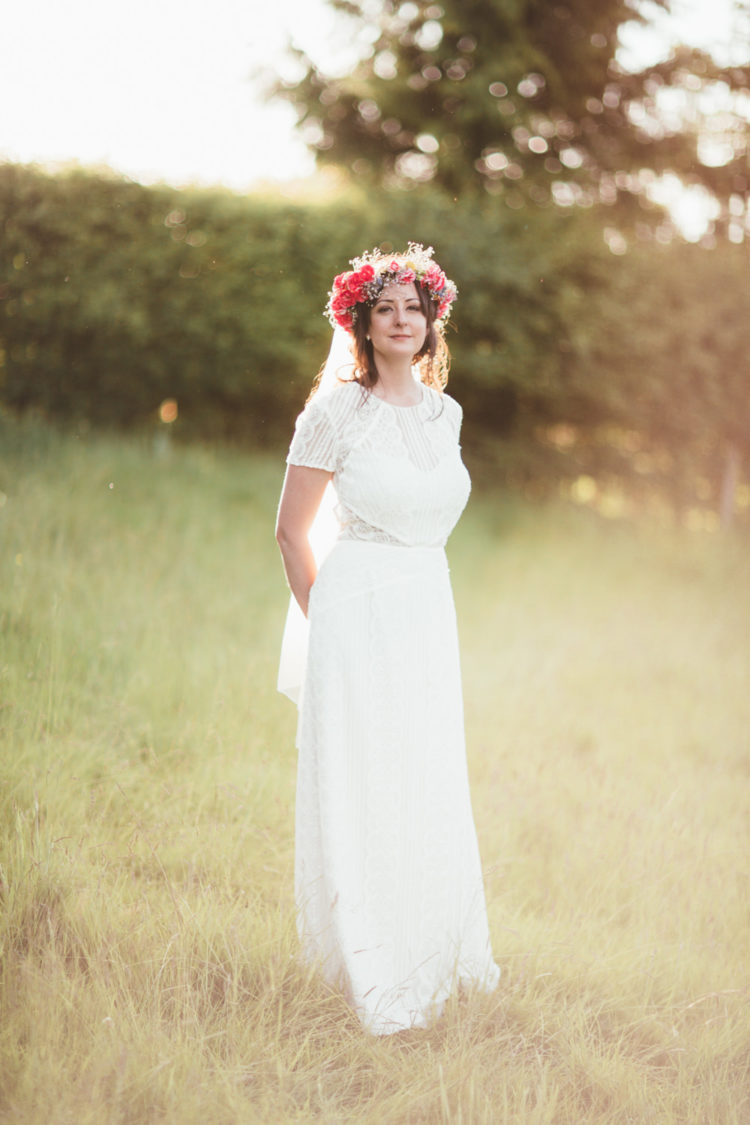 The bride was wearing a boho lace sheath wedding dress with short sleeves and illusion detailing