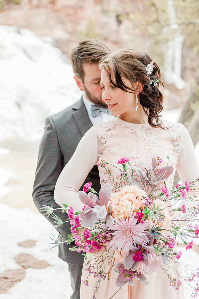 The bride was wearing a modern blush wedding dress and a matching top with floral appliques, rhinestone earrings and a hairpiece