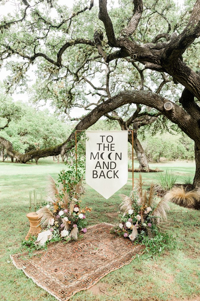 The wedding ceremony space was done with a copper arch with a banner, lush florals, greenery, pampas grass and a boho rug
