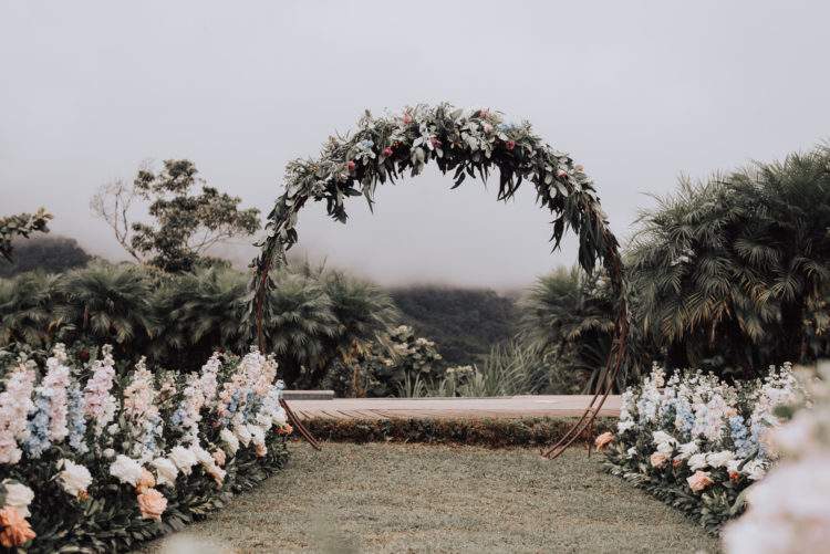 The wedding ceremony space was done with a lush greenery and flower arch and with lush blush and blue florals
