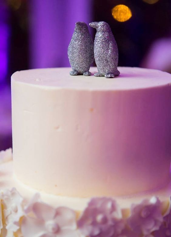 a couple of silver glitter penguins is a fun and whimsy winter wedding cake topper idea