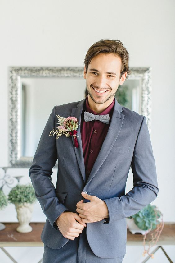 a fantastic groom's outfit with a grey suit and bow tie and a burgundy shirt for a bold statement