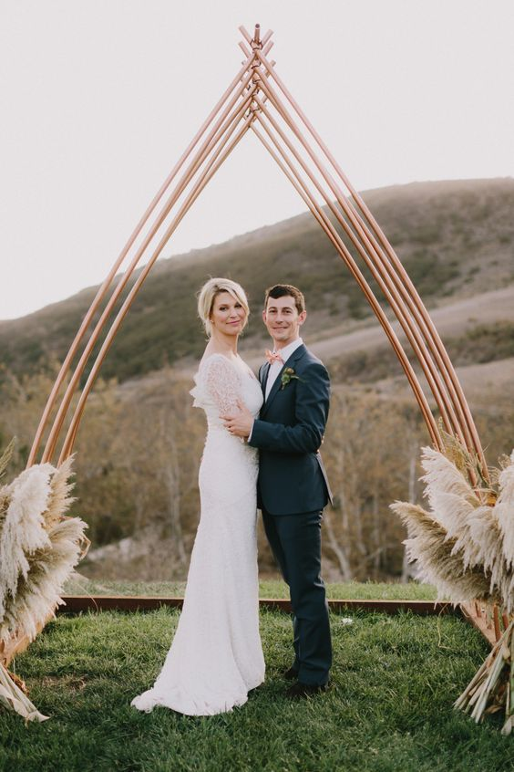 a stylish copper boho chic arch decorated with pampas grass is ideal for a boho chic wedding