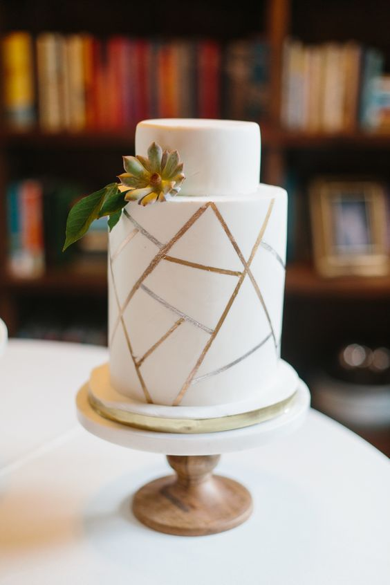 a white wedding cake with a crackle effect and greenery and a succulent is a simple and stylish idea