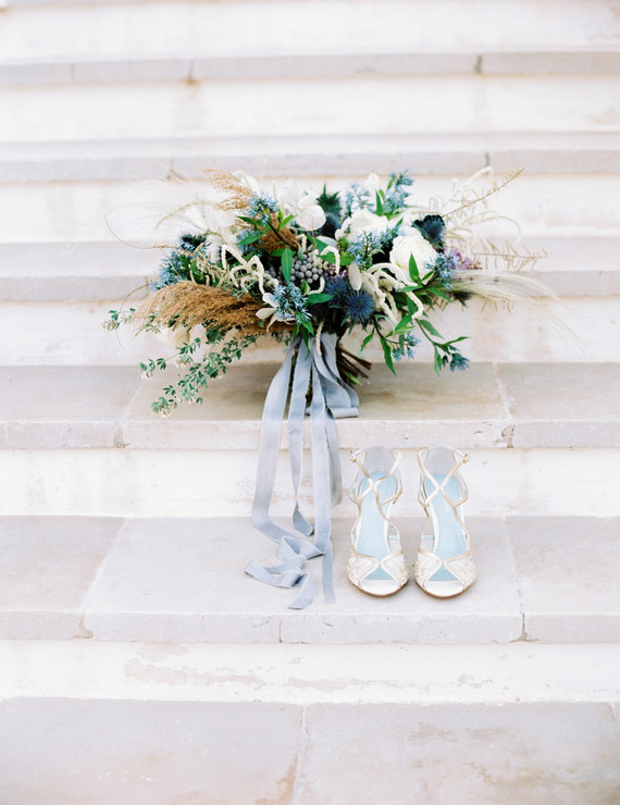 The bride was wearing lace shoes and was carrying a large undone wedding bouquet with plenty of texture