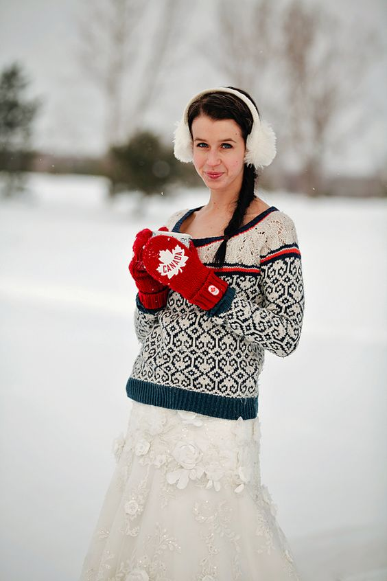 a bright patterned sweater, ear warmers and bright red mittens with maple leaves for an outdoor bride