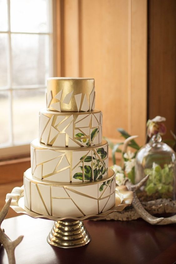 a chic gold and white geometric wedding cake with a crackle effect and a botanical pattern on the back