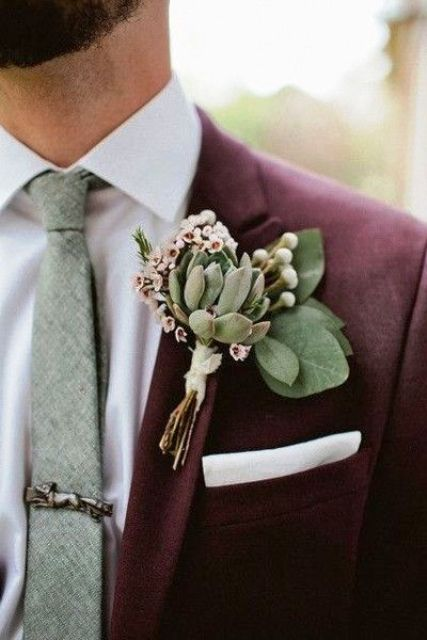 a succulent boutonniere with foliage and some tiny blooms that fit the suit's color at its best