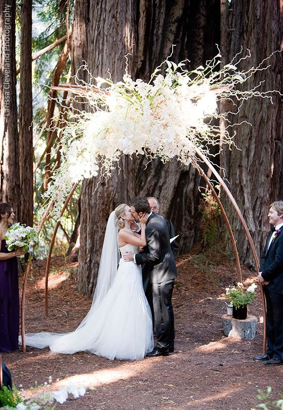 this white orchid wedding arch looks utterly magical in this ceremony among the redwoods