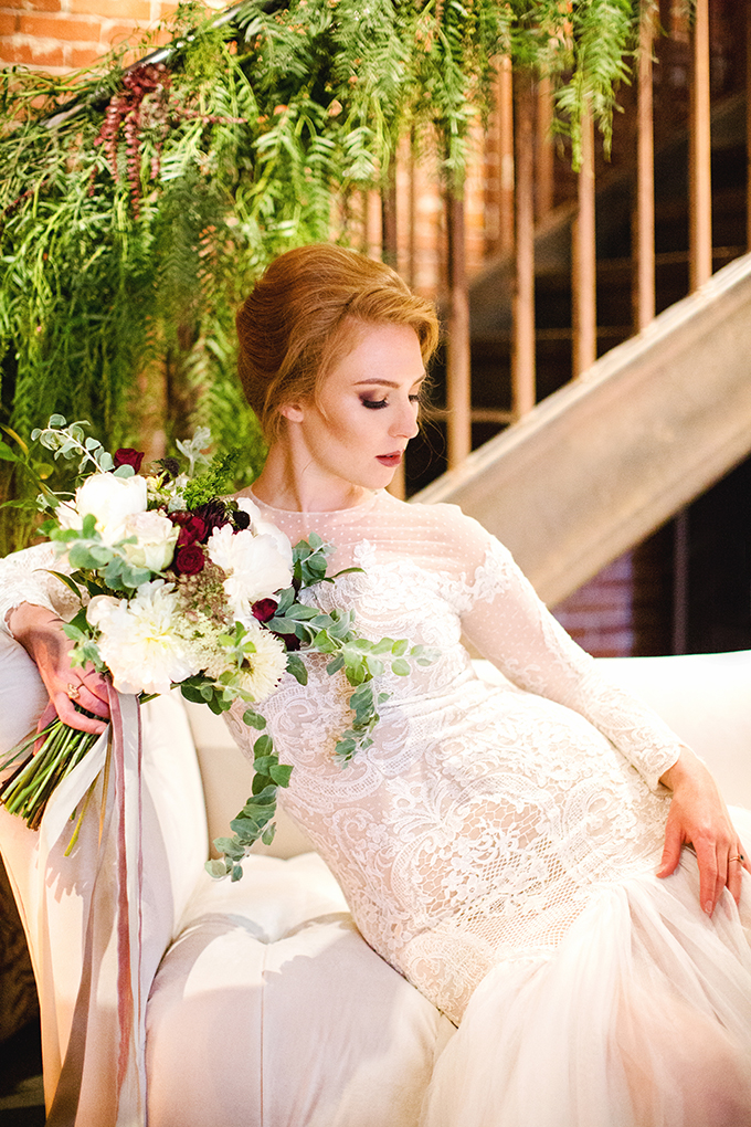 The bride was wearing a refined lace mermaid wedding gown with an illusion neckline, long sleeves, a burgundy lip