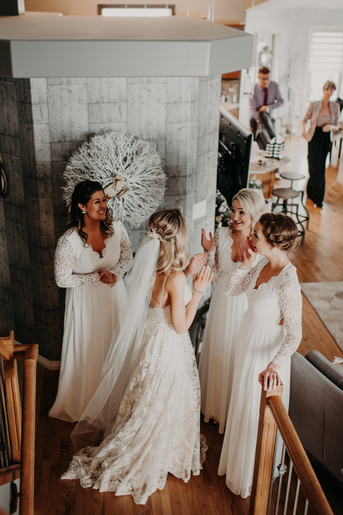 The bridesmaids were wearign all white wedding dresses with lace sleeves and bodices