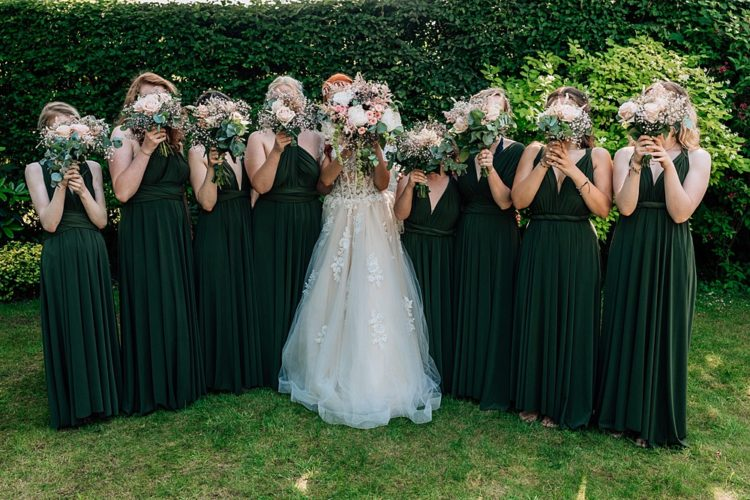 The bridesmaids were wearing forest green maxi gowns with a V-neckline