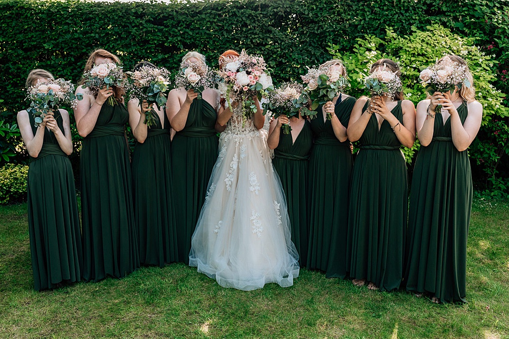 The bridesmaids were wearing forest green maxi gowns with a V neckline