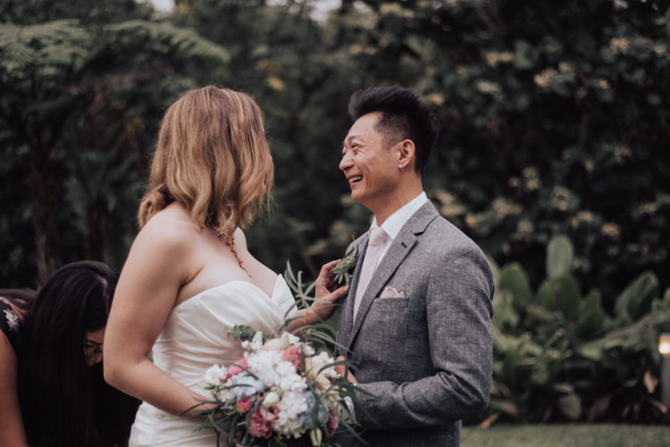 The groom was rocking a grey suit with a pale pink tie