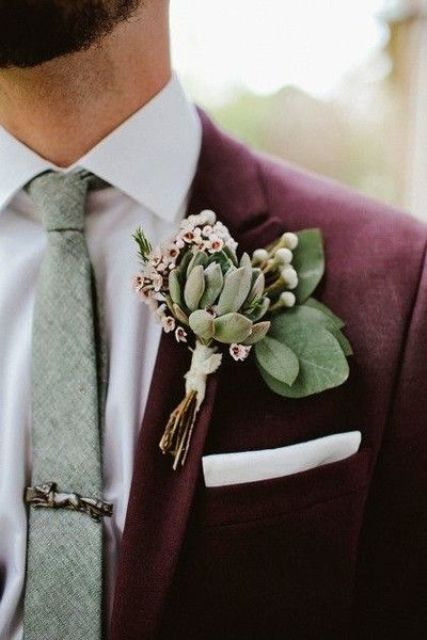 a burgundy suit, a white shirt, a grey tie and pale succulents for the boutonniere make up a bold and non-traditional groom look