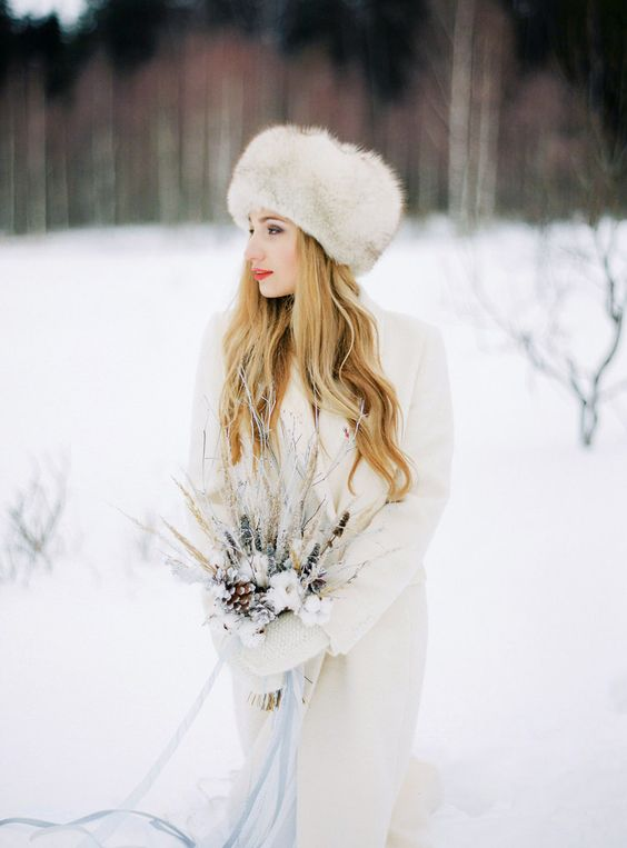 a neutral knit cardigan and matching mittens plus a faux fur hat for a snowy winter bride