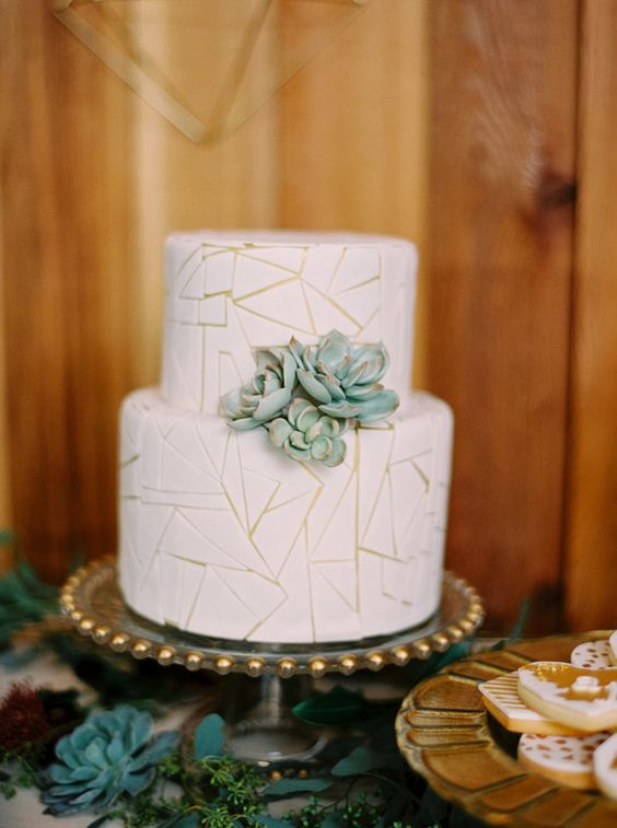 a white wedding cake with a crackle effect and succulents is a chic idea for a modern or desert wedding