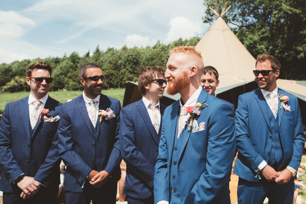 The groom and his best man were wearing three piece blue suits and the groomsmen were wearing navy