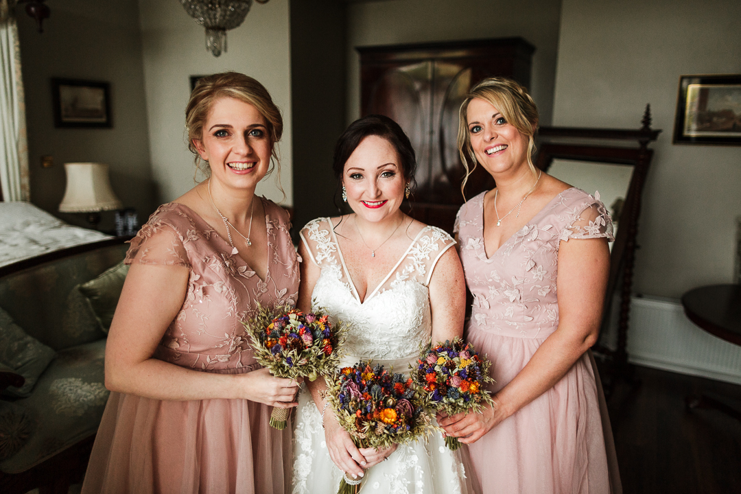 The bridesmaids were wearing dusty pink gowns with floral appliques