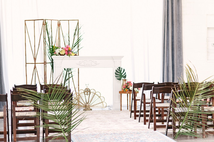 The ceremony space was styled with oversized tropical leaves and a faux mantel with lush tropical blooms