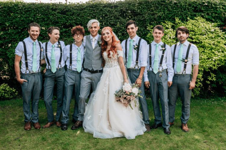 The groomsmen were wearing grey pants, suspenders and mint ties