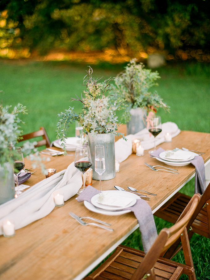 The table was left uncovered and there was an airy fabric runner plus foliage and bloom centerpieces in metal vases