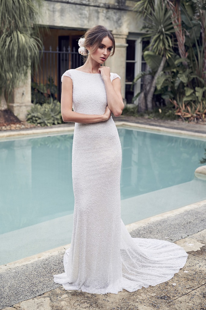 a sheath silver wedding dress with cap sleeves and a train plus a bateau neckline for a sparkly modern look