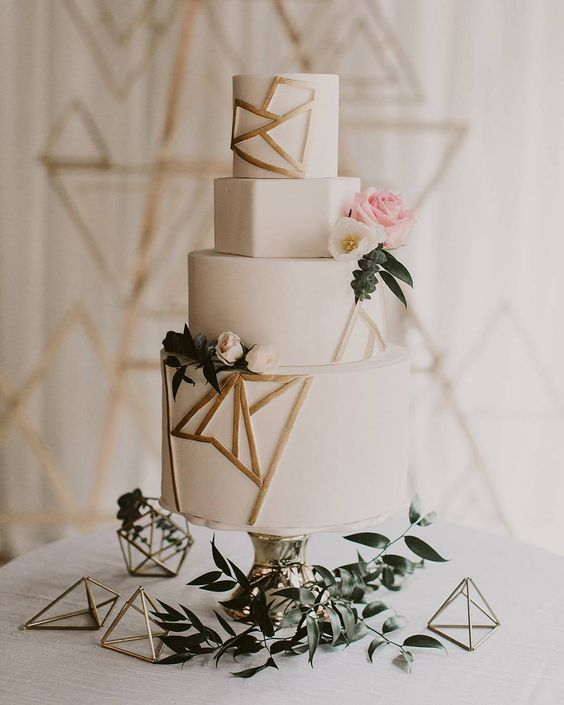 a white wedding cake with gold geometry, blooms and greenery for decorating is a romantic andcute option