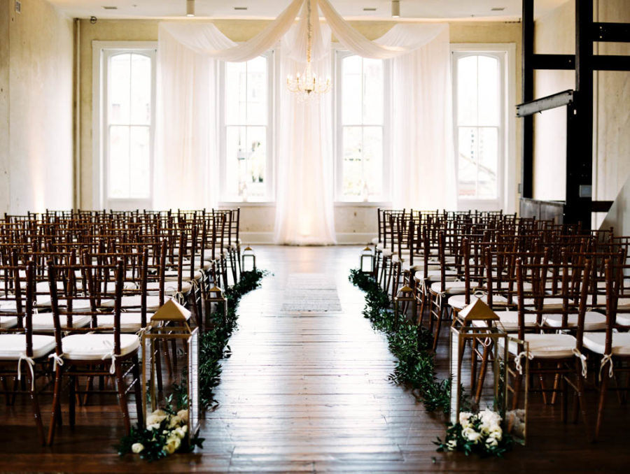 The wedding ceremony space was done with a fabric backdrop, lanterns, florals and greenery