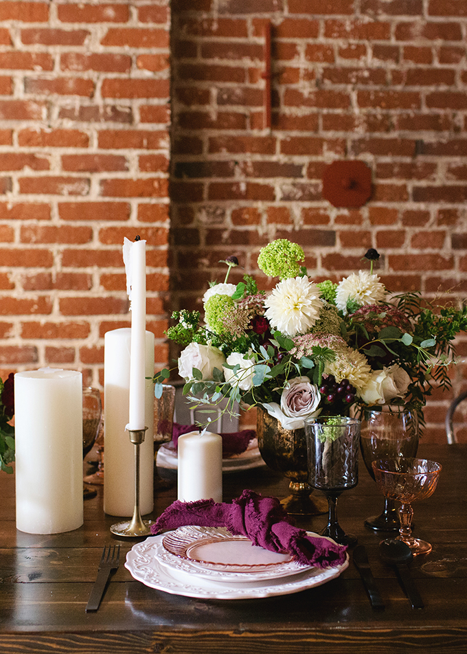 The wedding tablescape was done with an uncovered table, plum-colored napkins, large candles and lush florals