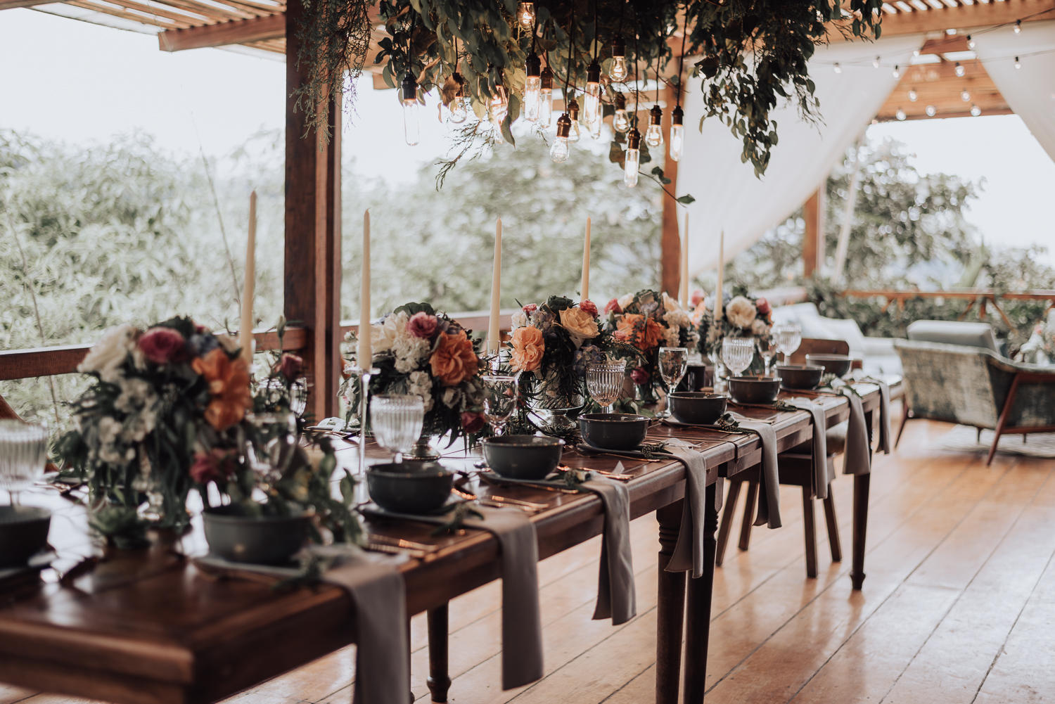 The wedding tablscape was done in greys and peach tones, with tall candles, lush florals and an Edison bulb and greenery chandelier