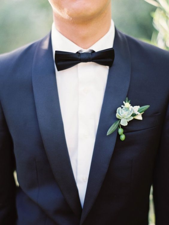an elegant boutonniere with a single succulent, berries and foliage on a classic tux