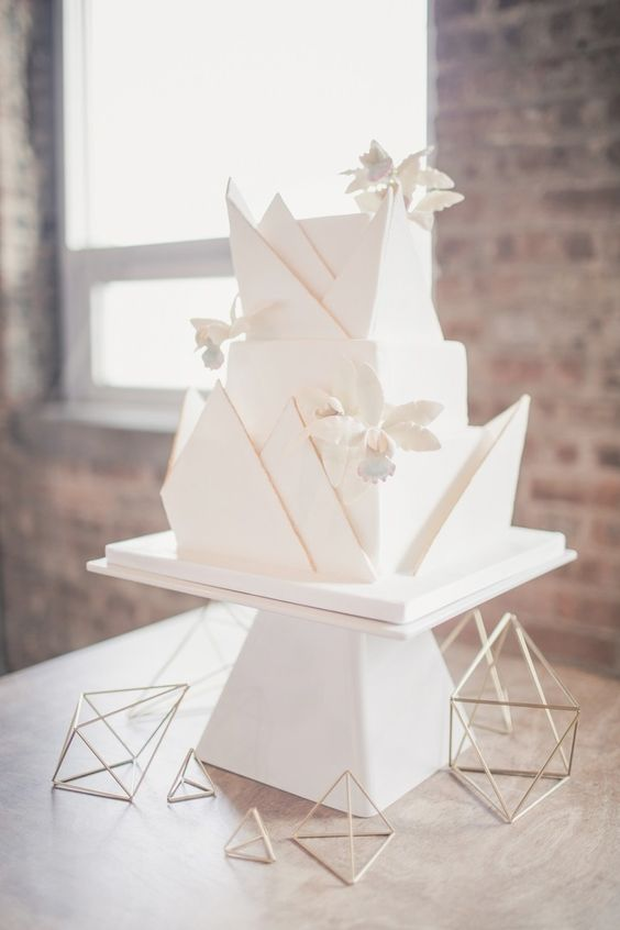 an ultra-modern white geometric wedding cake with a 3D effect and sugar flowers to make a statement
