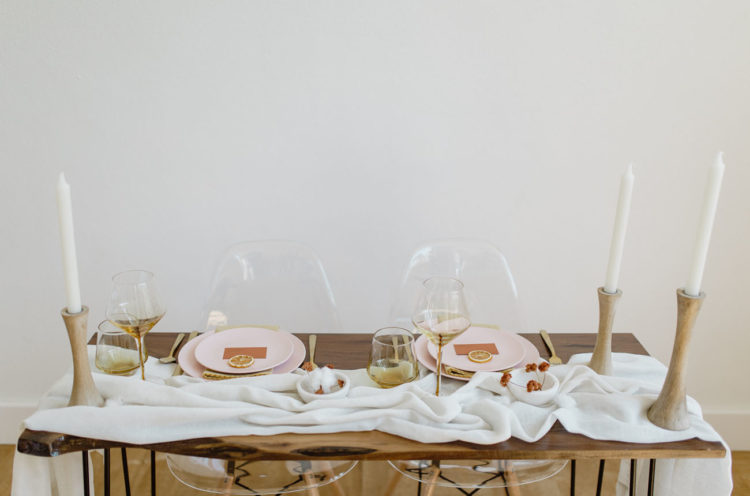 The sweetheart table was decorated with a fabric runner, wooden candle holdersm touches of gold and pink